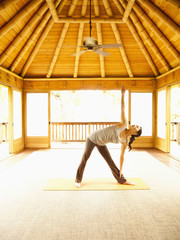Woman in triangle pose inside yoga and meditation pagoda at a luxury resort