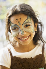 Close up of Hispanic girl with butterfly painted on face