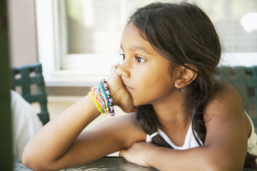 Pensive Hispanic girl with head in hands