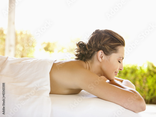 Smiling woman with eyes closed lying on massage table at luxury spa in Napa Valley California