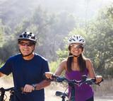 Hispanic couple walking with mountain bikes in remote area