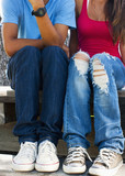 Close up of teenagers jeans as they sit together