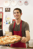 Caucasian teenager working in pizza restaurant