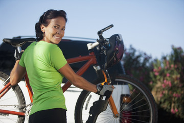 Caucasian woman putting bicycle on car rack