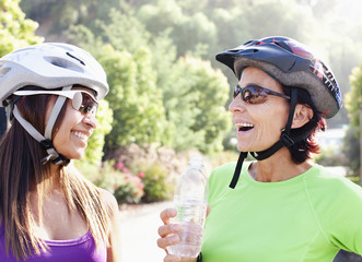 Smiling women in sunglasses and bike helmets drinking water