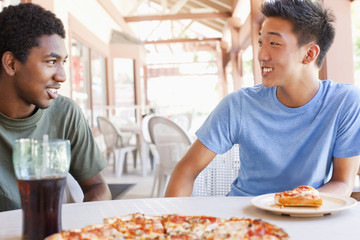 Friends eating pizza in restaurant
