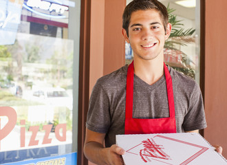 Caucasian teenager holding pizza box in restaurant