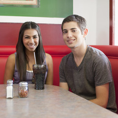 Teenage couple sitting together in restaurant