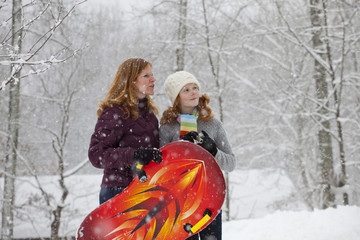 Caucasian mother and daughter standing in snow with sled