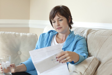 Caucasian woman on sofa reviewing bills