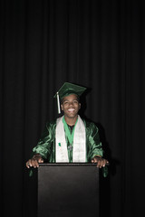 Mixed race high school graduate standing at podium