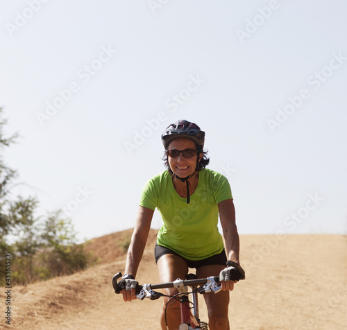 Caucasian woman riding mountain bike on dirt road