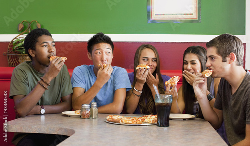 Friends eating pizza together in restaurant
