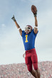 Mixed race football player with arms raised holding football