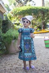 Caucasian girl in dress, sunglasses and hat