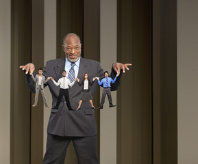 African American businessman holding string of small business people
