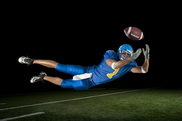 Mixed race football player jumping in mid-air catching football