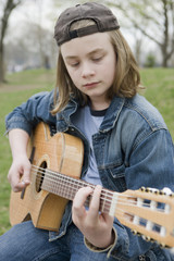 Caucasian boy playing acoustic guitar