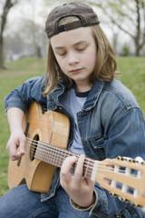 Caucasian boy playing acoustic guitar