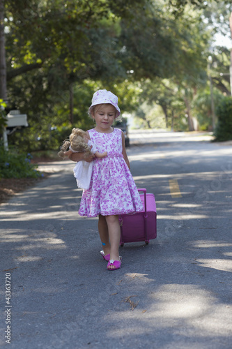 Caucasian girl in dress walking down street with rolling luggage