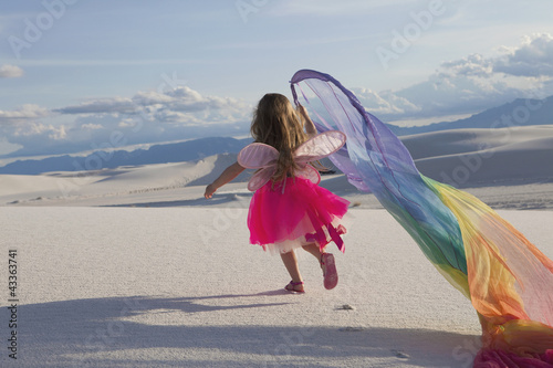 Caucasian girl in fairy costume in desert