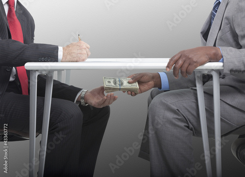 Businessman handing stack of cash under table to co-worker