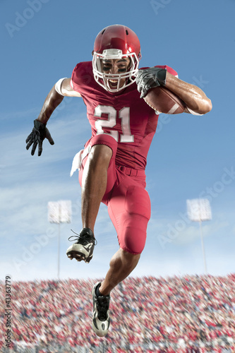 African American football player running with football