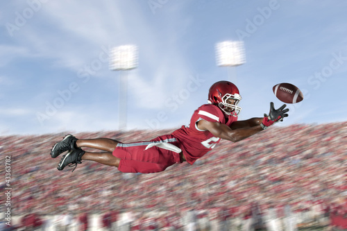 African American football player jumping in mid-air catching football