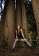 Woman leaning against tree trunk in forest