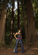 Woman in bell bottoms standing in forest