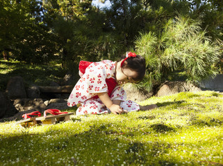 Mixed race girl in garden wearing kimono