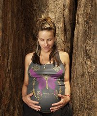 Caucasian woman caressing pregnant stomach near tree trunk