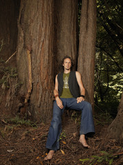 Barefoot Caucasian man leaning against tree trunk