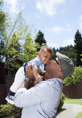African American father lifting and kissing baby son