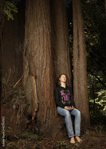 Caucasian woman sitting on tree trunk in forest