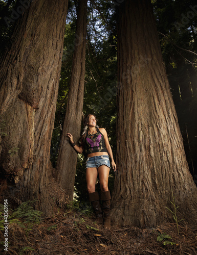 Caucasian woman leaning against tree trunk