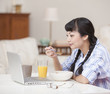 Asian woman in pajamas eating breakfast and using laptop