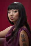 Elegant Asian woman with tattoo on arm