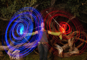 Black woman making blue and red light streaks in air