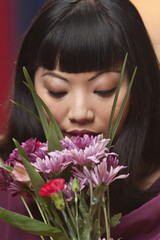 Elegant Asian woman smelling bouquet of flowers