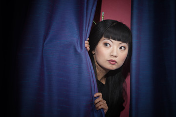 Anxious Asian woman peering out from behind stage curtains