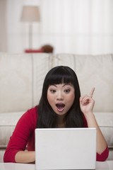 Surprised Asian woman sitting on floor in livingroom with laptop