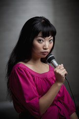 Asian woman singing into microphone