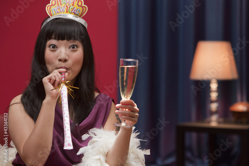 Elegant Asian woman drinking Champagne on New Year's Eve