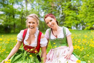 Junge Frauen in traditionellem Dirndl auf einer Frühlingswiese