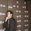 Confused businessman standing with boxes