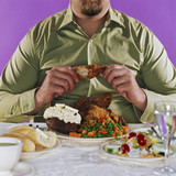 Overweight man eating fried chicken dinner