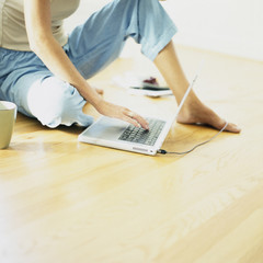 Woman using laptop on floor