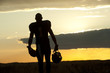 Silhouette of Black football player carrying helmet and football