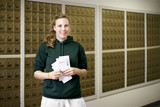 Smiling Caucasian woman holding letters in mailroom